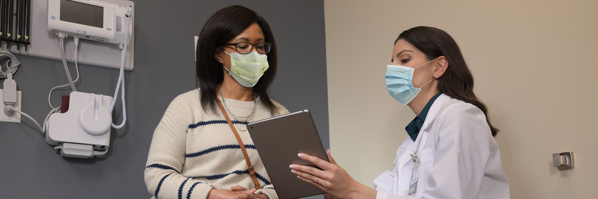 Woman reviewing information on tablet with provider