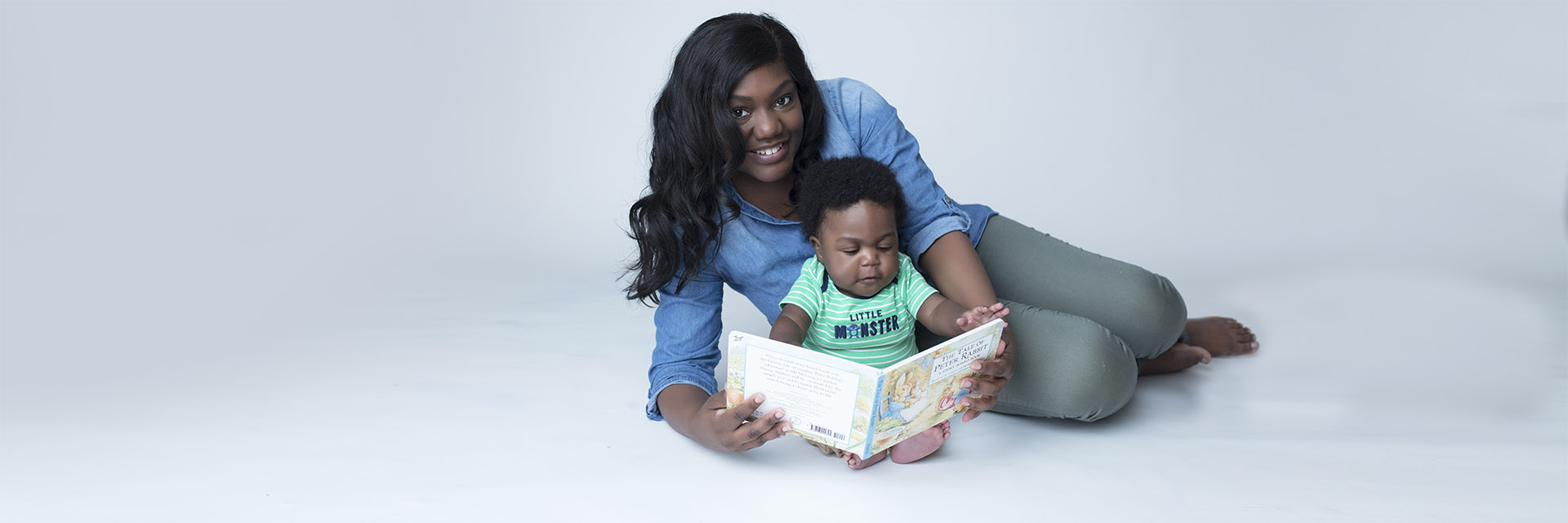 Mom and Baby on Floor Holding a Book