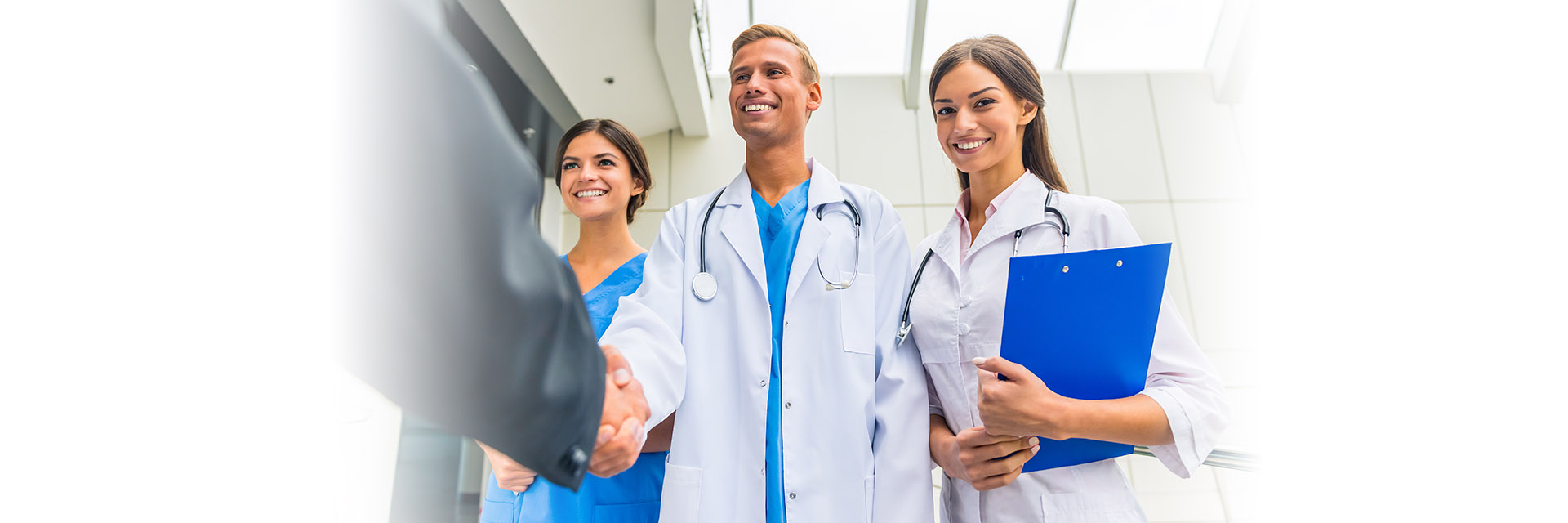 Group of healthcare workers greeting business person