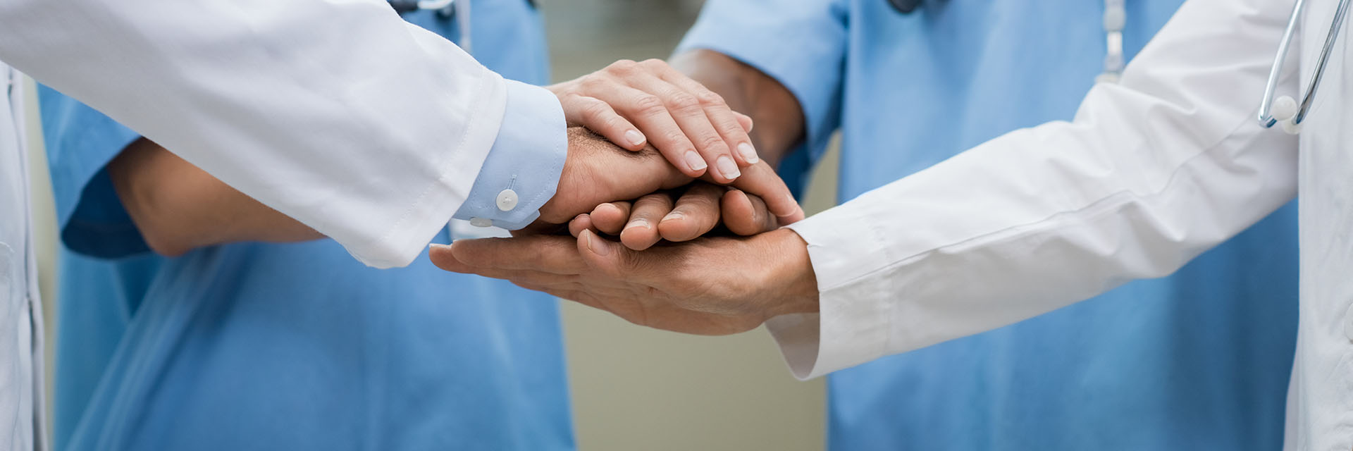Provider hands stacked on top of each other