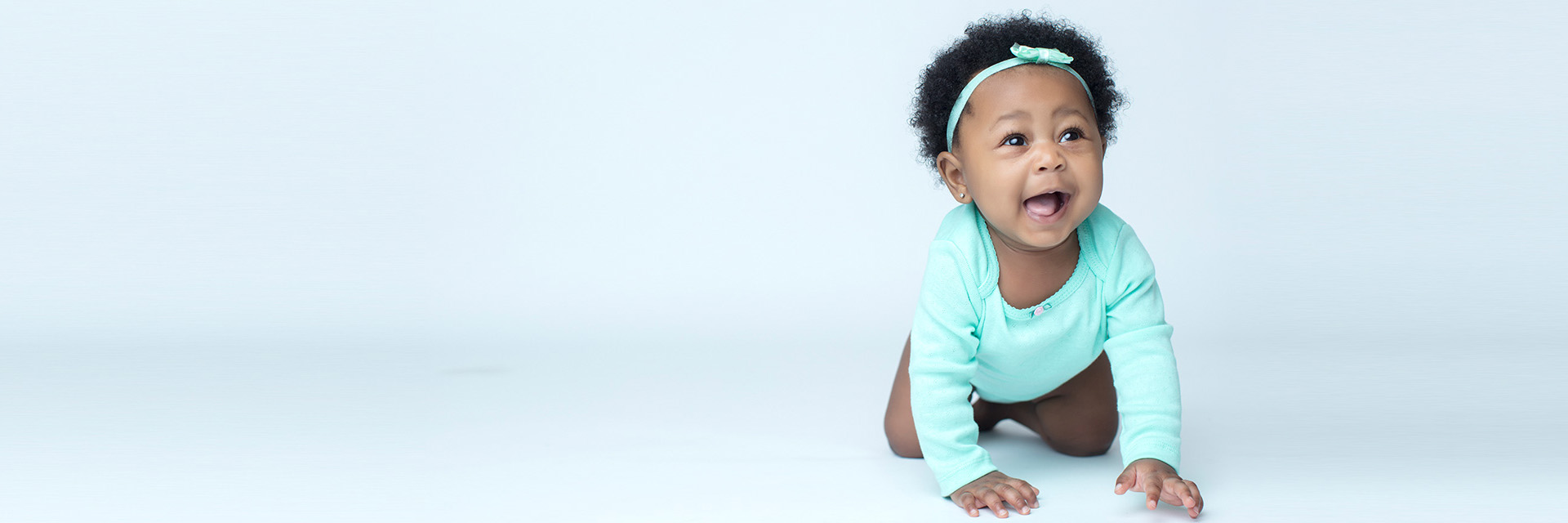 African American Baby in Teal Crawling on Floor
