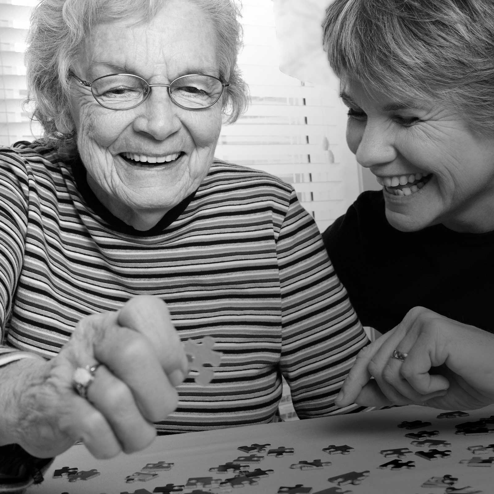 Mature woman and daughter working a puzzle