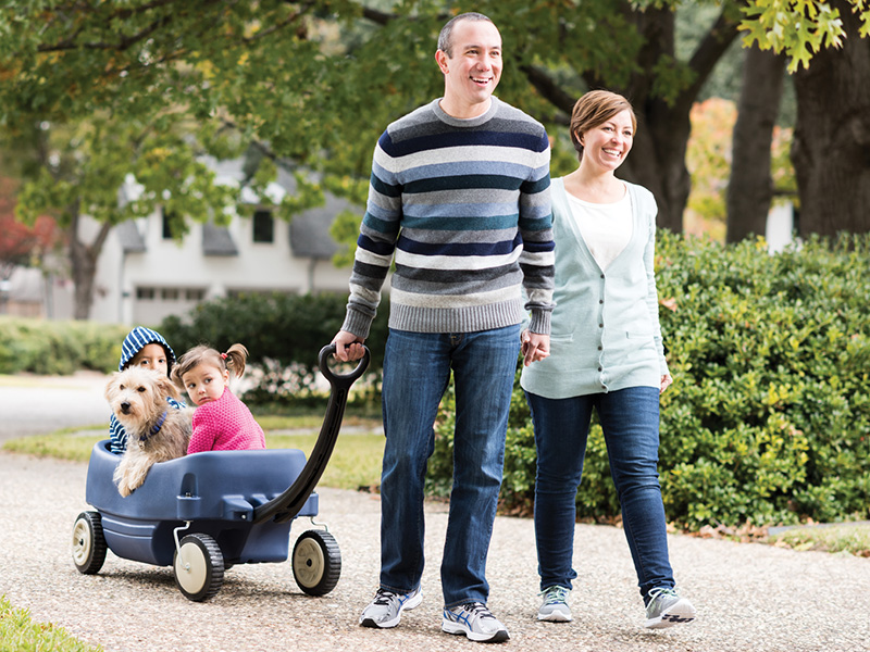 Family walks outside pulling their kids in a wagon