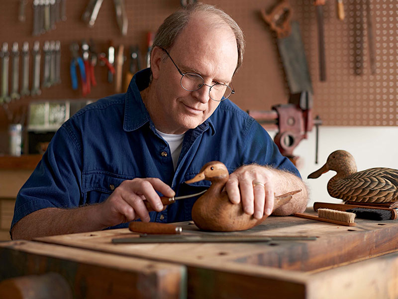 Man carving wooden duck