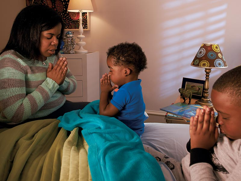 Mother and children praying in bed