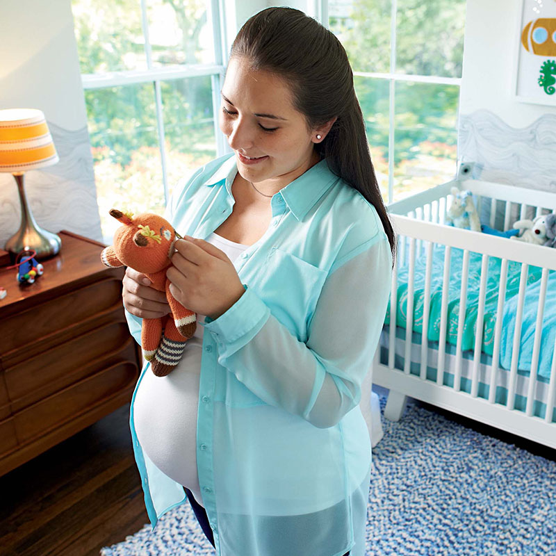 Pregnant woman in Nursery Holding Stuffed Toy