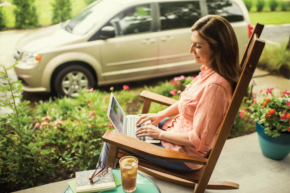 Woman on laptop in rocking chair outside