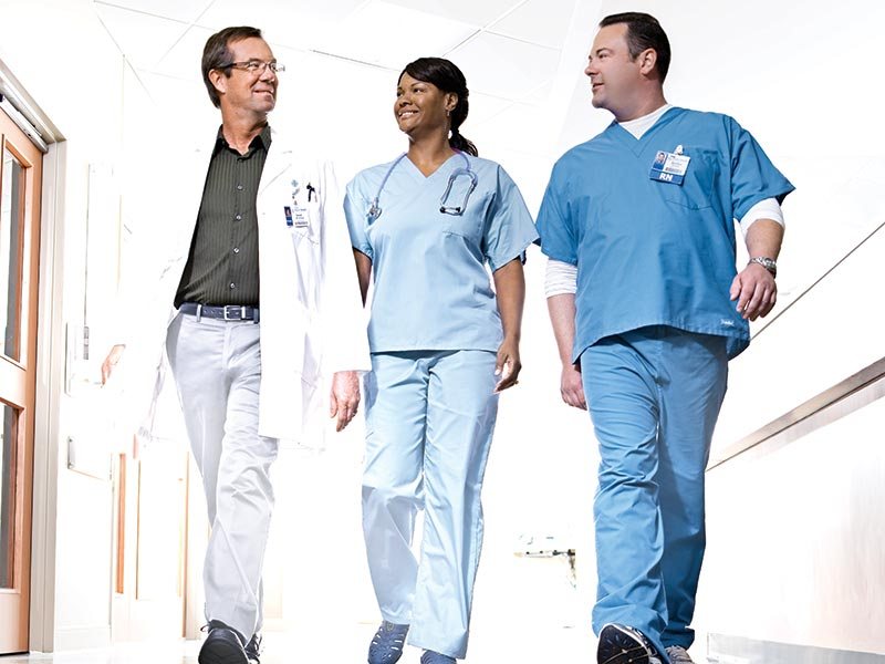 Physician and Nurses Walking in Hallway