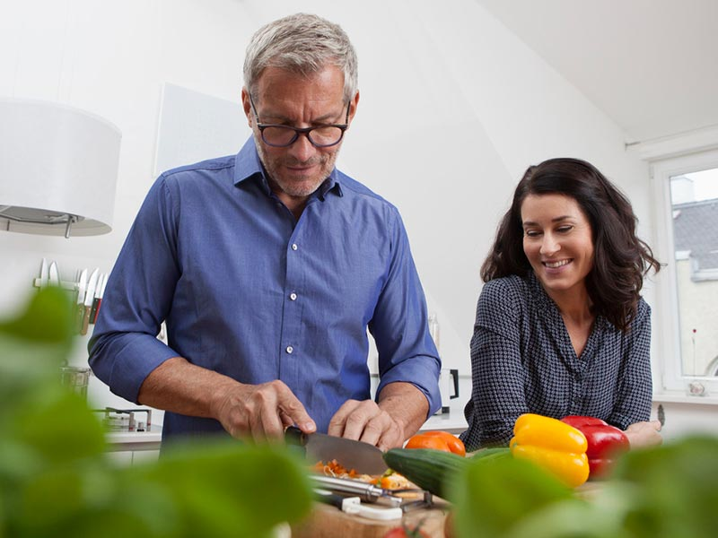 Couple cutting food in kitchen